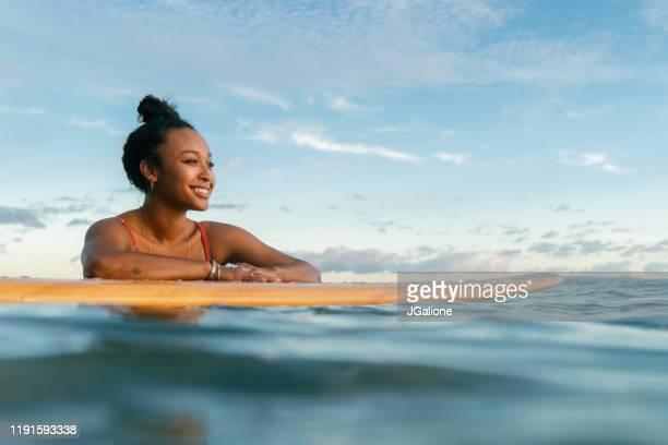jonge vrouw rusten op haar surfplank wachten op een golf - afro amerikaanse etniciteit stockfoto's en -beelden