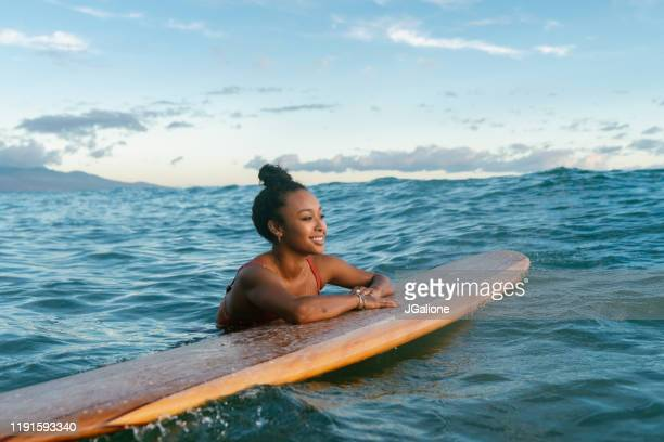 young woman resting on her surfboard waiting for a wave - hawaii islands stock pictures, royalty-free photos & images