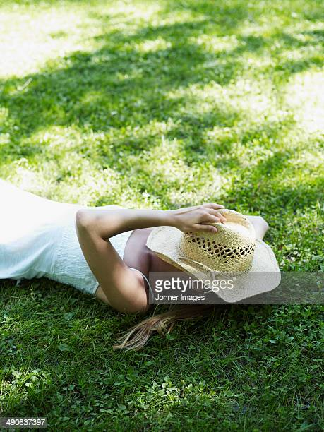 Young woman resting on lawn with hat on face