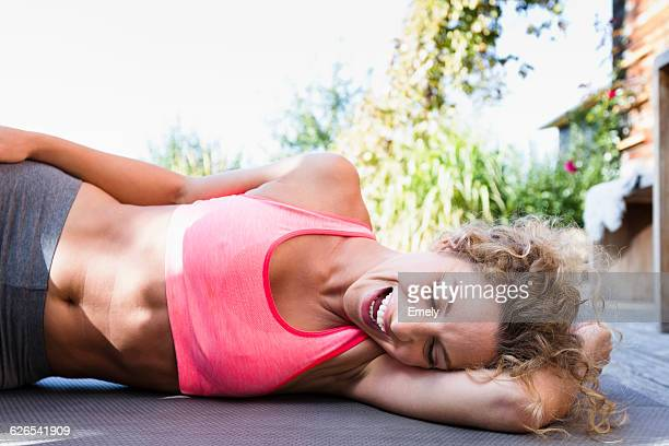 young woman resting on yoga mat in pink crop top, laughing - crop top stock pictures, royalty-free photos & images