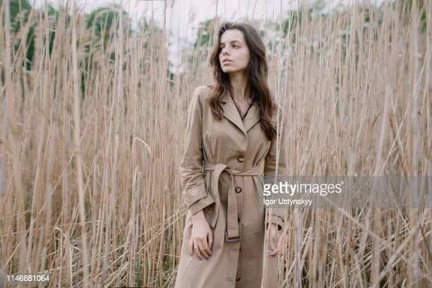 young woman resting outdoors - trench coat stock pictures, royalty-free photos & images