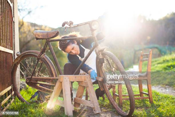 Young Woman Restoring Obsolete Vintage Bicycle
