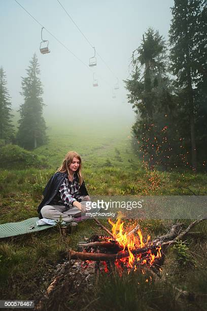 Young woman rests by campfire.