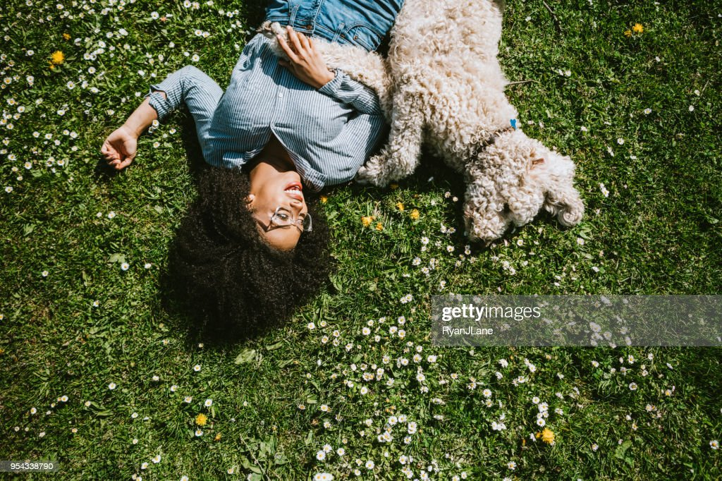 A Young Woman Rests in the Grass With Pet Poodle Dog : Stock Photo
