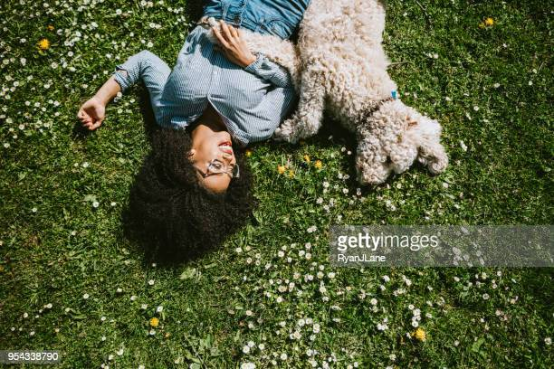 a young woman rests in the grass with pet poodle dog - lying down foto e immagini stock