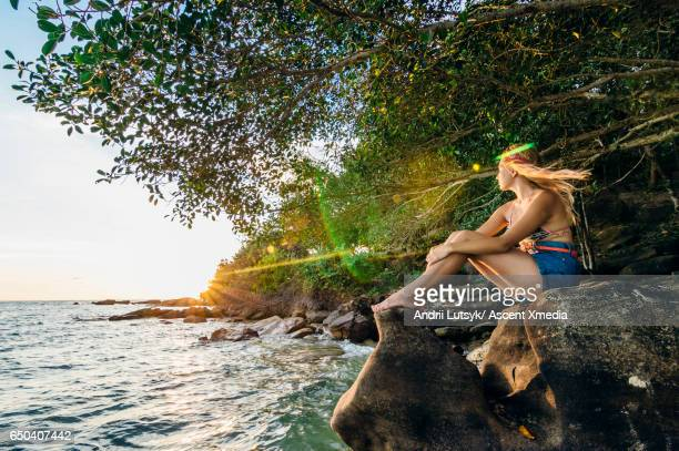 Young woman rests on ocean rocks, watches sunset