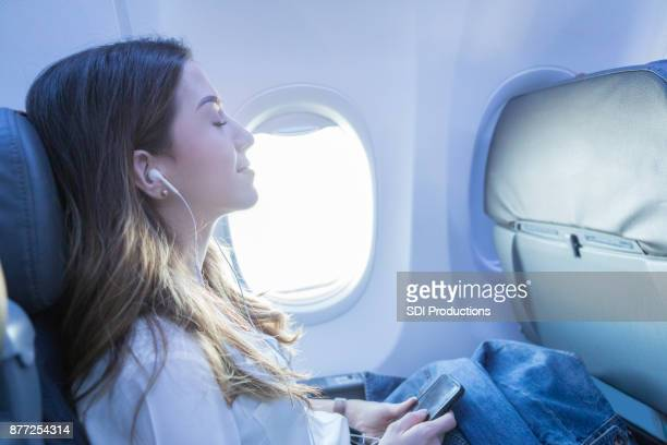 young woman rests with music during air travel - serene people stock pictures, royalty-free photos & images