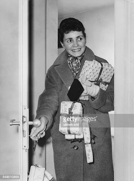 Young woman returning from shoppiing with christmas gifts late fifties