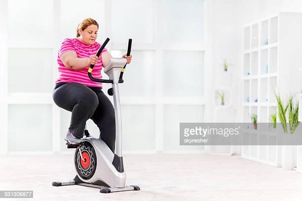 Young woman ridding exercising bike.