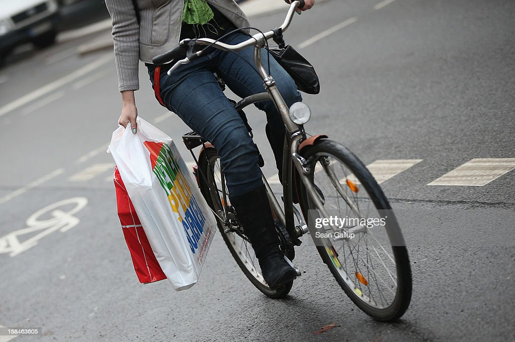 A young woman rides a bicycle as she carries shopping bags on a busy shopping street in Steglitz district on December 17, 2012 in Berlin, Germany. Retailers are hoping for a strong Christmas season in Germany, one of the few countries whose economy has so far weathered the current Eurozone debt crisis relatively well.