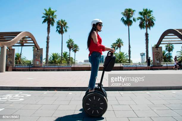 Young woman rides a segway scooter near the beach in Barcelona on August 10, 2017. - Spanish activists in recent weeks have launched initiatives...