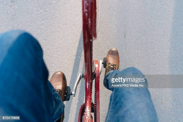 young woman rides bicycle, on residential street - pedal stock pictures, royalty-free photos & images