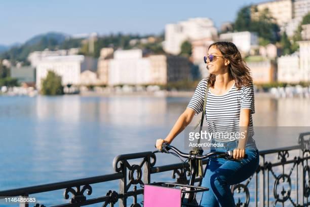 若い女性は自転車と笑顔に乗る - スイス ルガーノ ストックフォトと画像