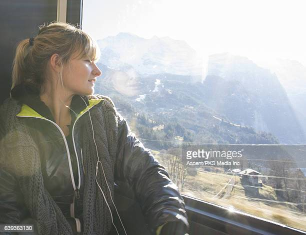 Young woman rides train above valley, mountains
