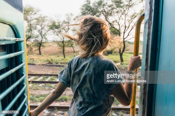 Young woman rides train through rural area
