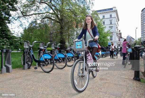Young woman riding a bicycle from Barclays Cycle Hire at Hyde Park on May 12 2012 in London United Kingkom