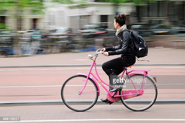 young woman riding a bicycle in amsterdam, holland. - ogphoto stock pictures, royalty-free photos & images
