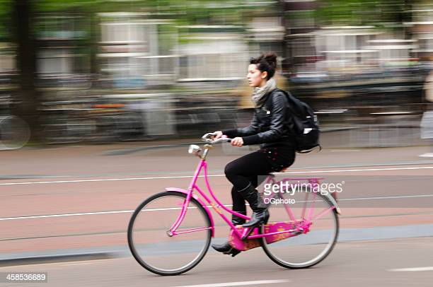 young woman riding a bicycle in amsterdam, holland. - ogphoto stock photos and pictures