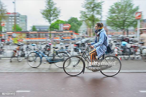 Young woman riding a bicycle in Amsterdam.