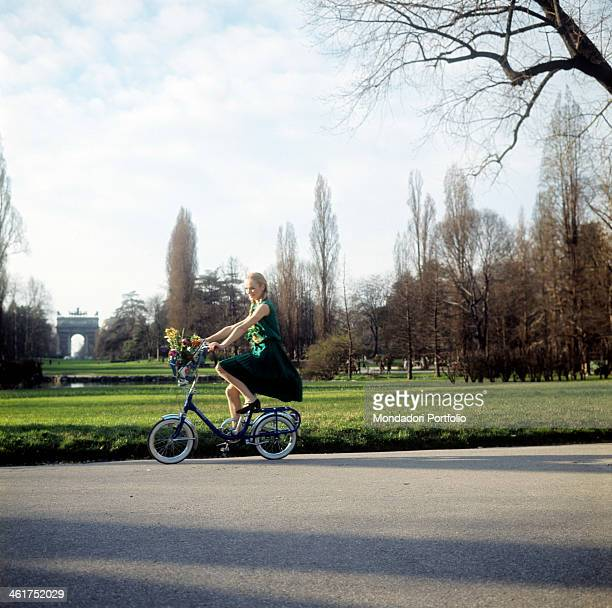 A young woman riding a bicycle in the Parco Sempione In the background the Arco della Pace Milan 1967