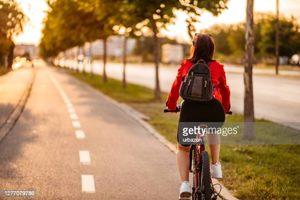 young woman riding a bicycle - bicycle lane stock pictures, royalty-free photos & images