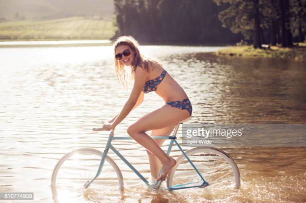 Young woman riding a bicycle through a lake