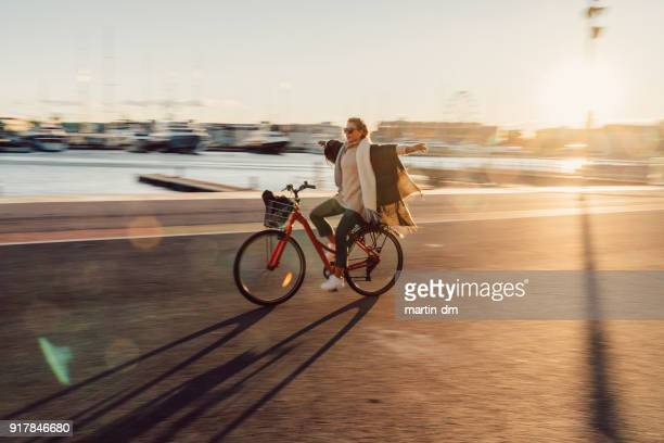 young woman riding a bicycle with hands outstretched - solar flare stock pictures, royalty-free photos & images