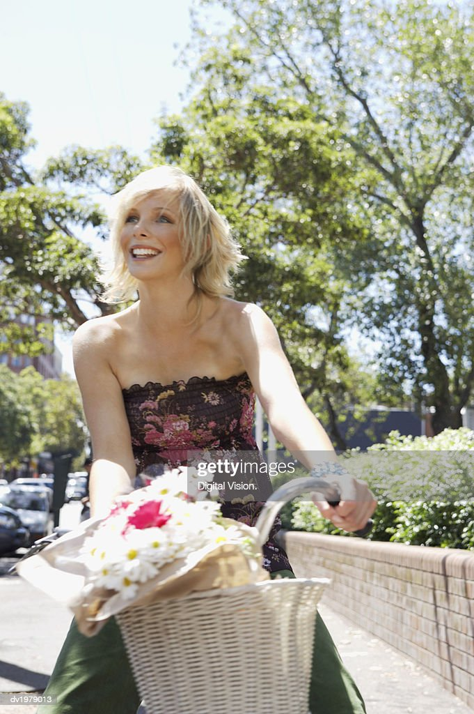 Young Woman Riding a Bike with a Basket Full of Flowers : Stock Photo