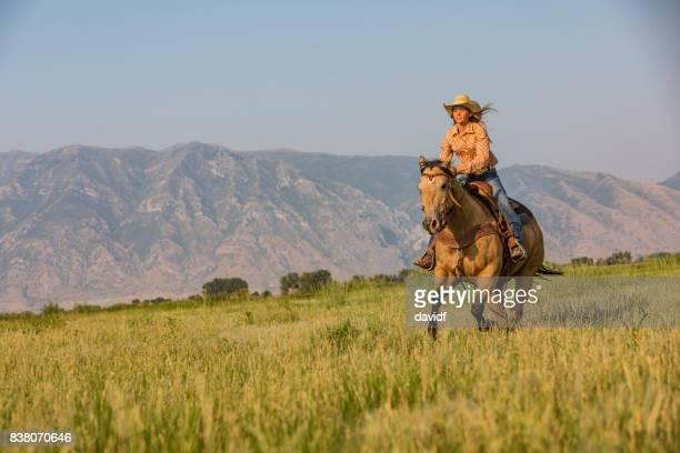 jeune femme à monter à cheval à travers la prairie - cowgirl photos et images de collection