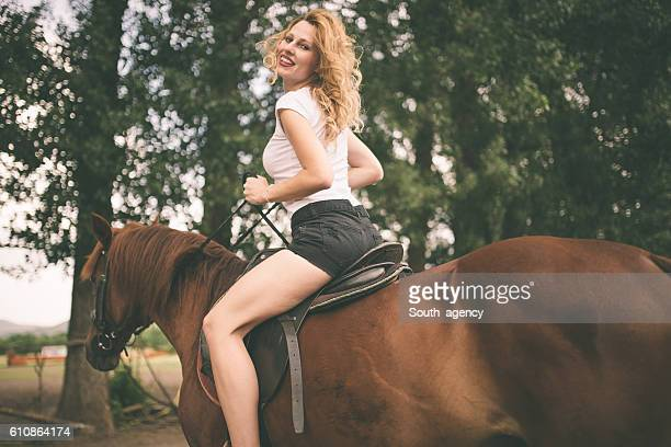 Young woman riding a horse looking back