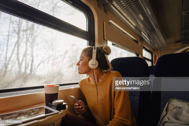 young woman riding a train - train vehicle stock pictures, royalty-free photos & images