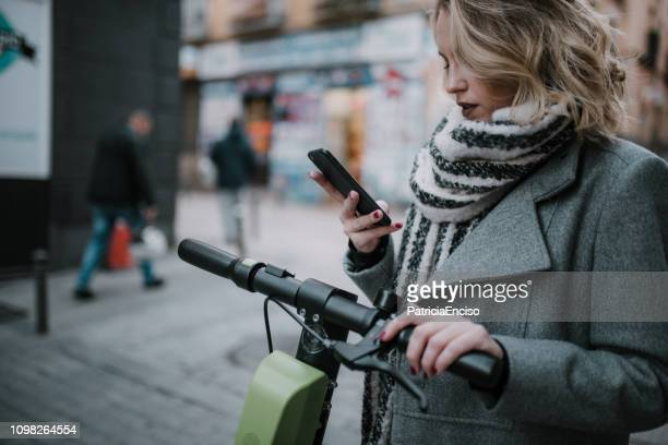 young woman riding an electric scooter in a city - electric scooter stock pictures, royalty-free photos & images
