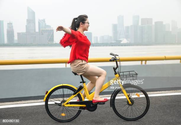 Young woman riding bicycle against city skyline,Hangzhou,China