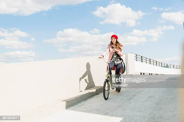 Young woman riding bicycle holding cell phone