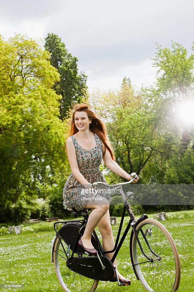 Young woman riding bicycle in grass : Stockfoto