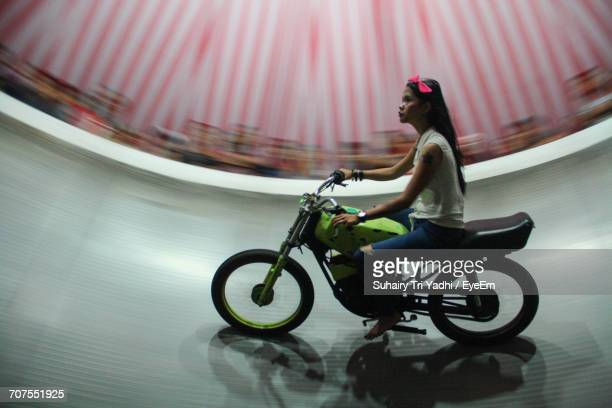 Young Woman Riding Bicycle In Wall Of Death