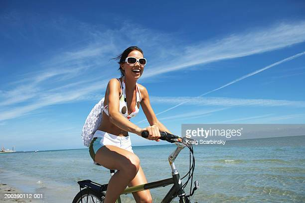 Young woman riding bicycle on beach, smiling, portrait, close-up