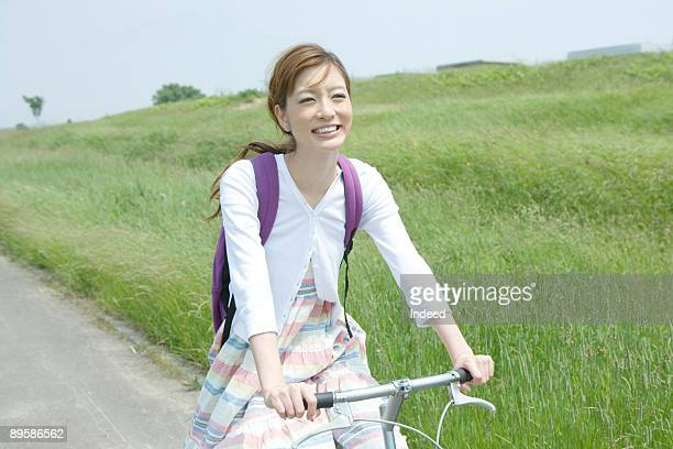 Young woman riding bicycle on path