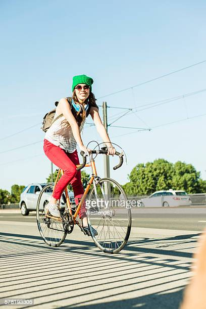 Young woman riding bicycle on pavement at the street