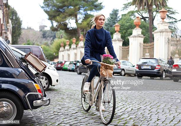 young woman riding bicycle on Roman cobbled road