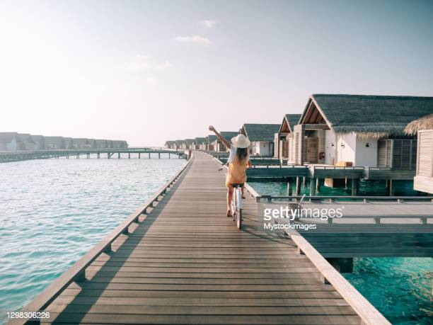 young woman riding bicycle on wooden pier in the maldives - maldives stock pictures, royalty-free photos & images