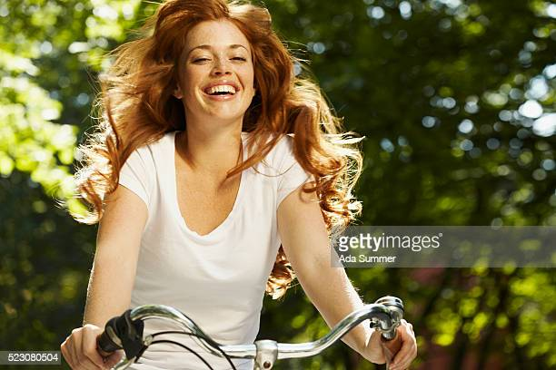 young woman riding bicycle, smiling - capelli mossi foto e immagini stock