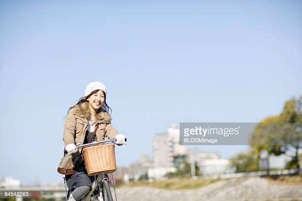 Young woman riding bicycle, smiling