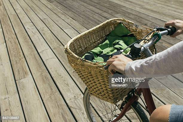 young woman riding bicycle with basket, close up - montare foto e immagini stock