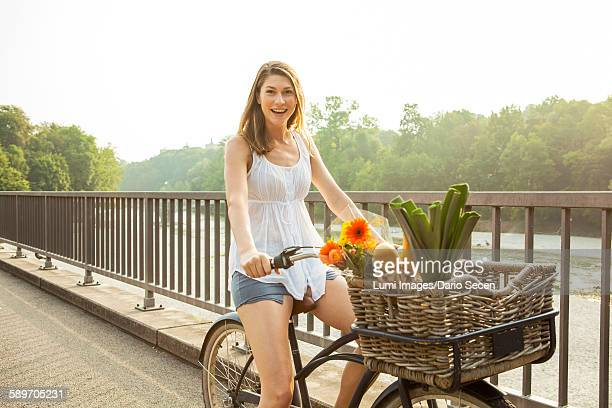 Young woman riding bicycle with shopping basket