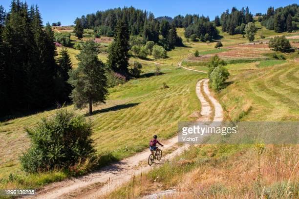 jonge vrouw die fiets langs onverharde weg berijdt die door grasgebieden en bloemen in een berggebied wordt omringd - bulgarije stockfoto's en -beelden