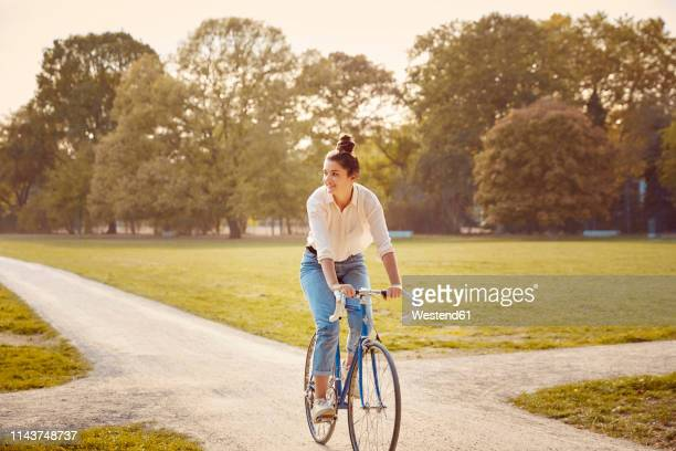 young woman riding bike at a park - radfahren stock-fotos und bilder