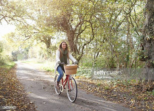 Young woman riding bike in countryside.