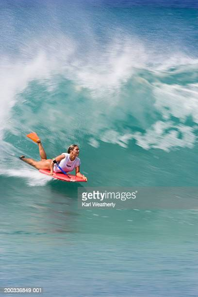 Young woman riding boogie board in wave