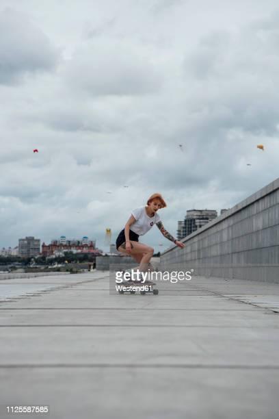 young woman riding carver skateboard on a promenade - longboard skating stock-fotos und bilder